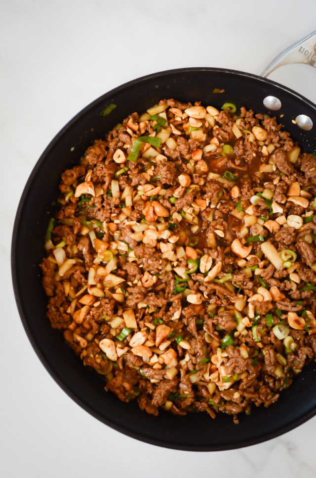 A skillet full of ground turkey, green onions, water chestnuts and cashews in an Asian sauce.