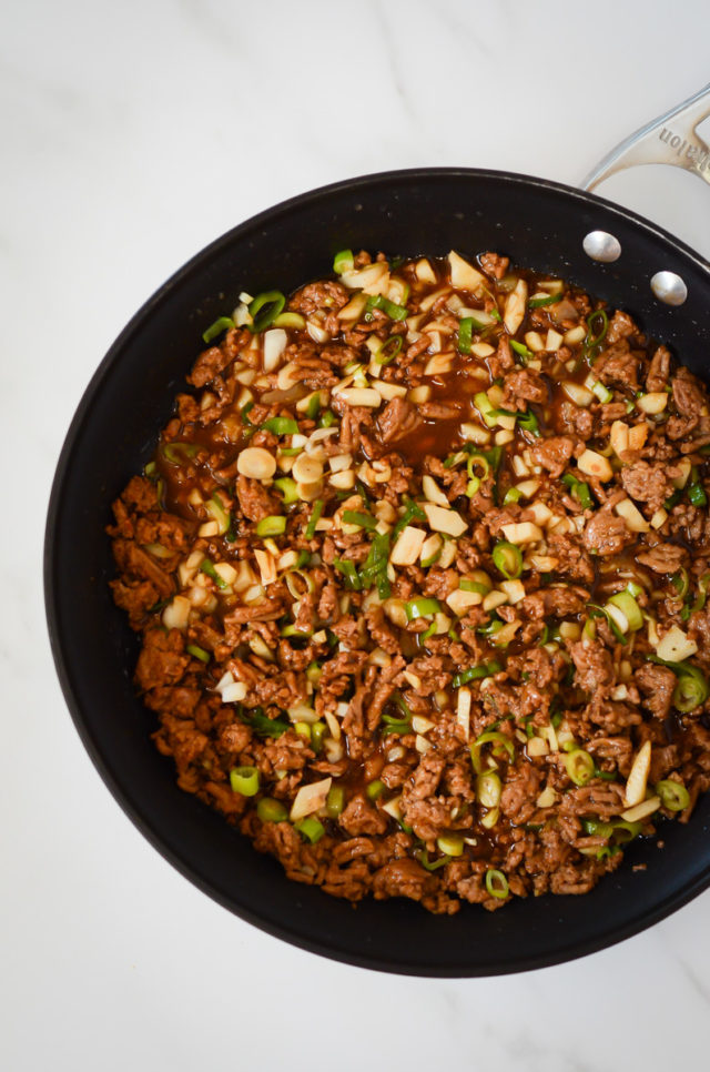 A skillet full of ground turkey, water chestnuts and green onions.