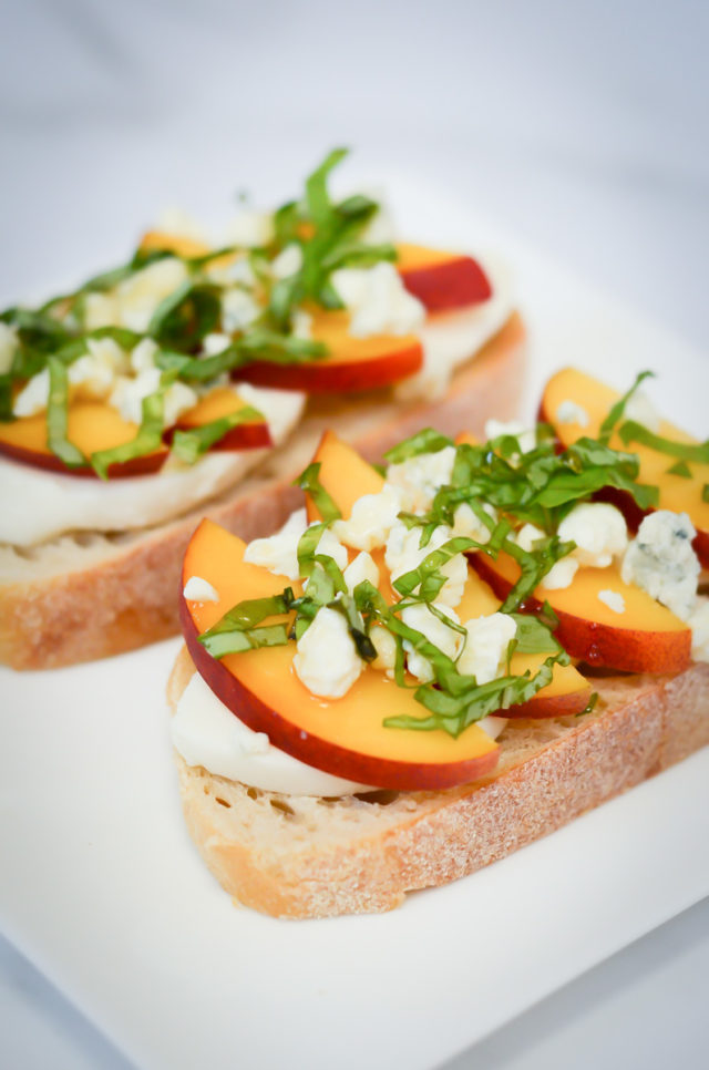 Two pieces of bread topped with mozzarella, peaches, blue cheese, basil and honey.