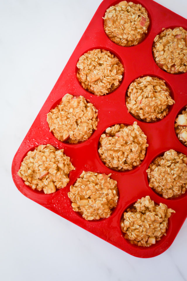 Pumpkin apple baked oatmeal batter divided into silicone muffin tins.