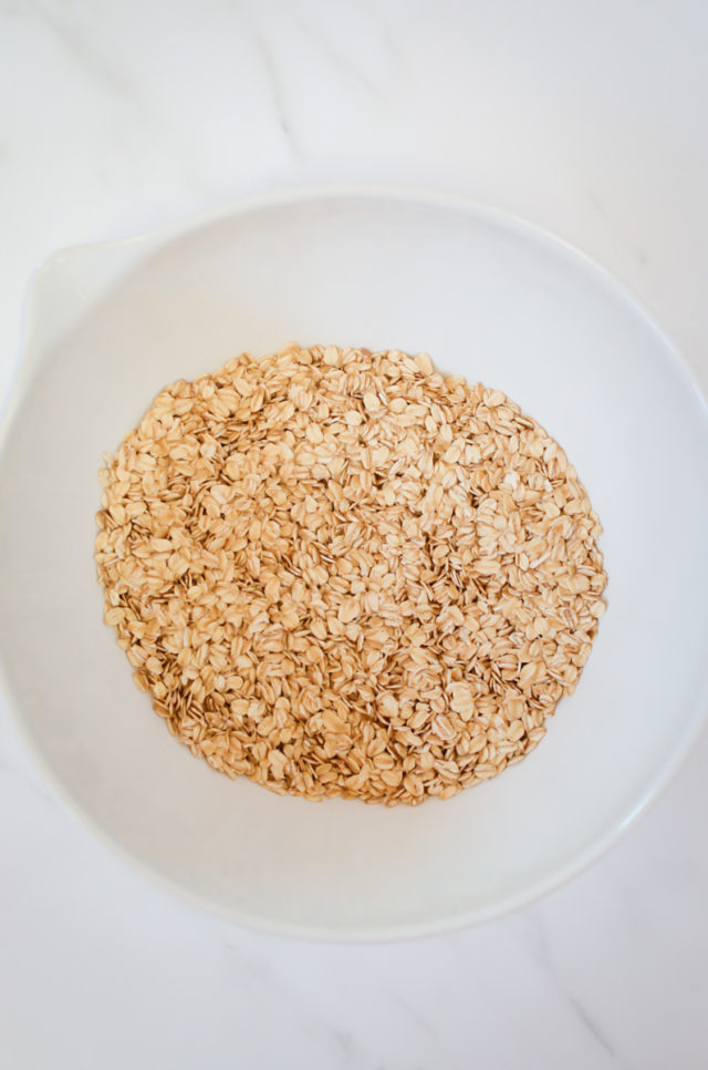 A white mixing bowl of the dry ingredients for oatmeal cups.