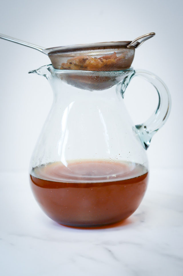 A sieve with apple cider discards over a glass pitcher of apple cider.