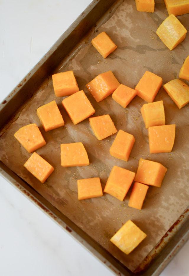 Cubed butternut squash on a sheet pan.