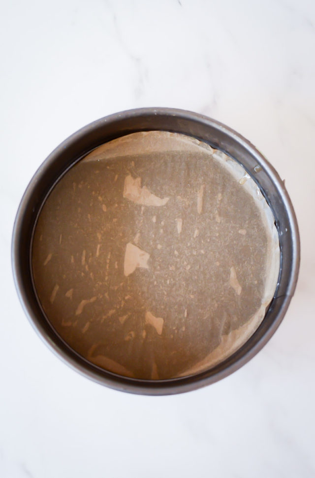 A springform pan lined with parchment paper.