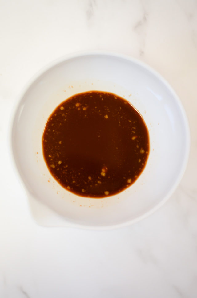 An overhead shot of a white bowl of stir-fry sauce.