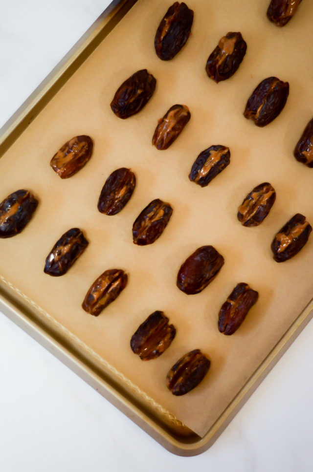 An overhead shot of a tray of dates stuffed with almond butter.