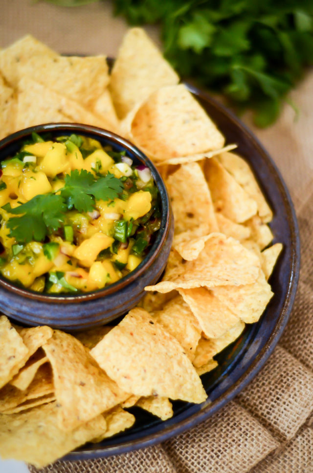 A bowl of mango salsa surrounded by tortilla chips.