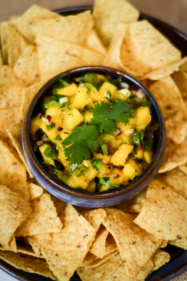 A close-up of a bowl of mango salsa surrounded by tortilla chips.