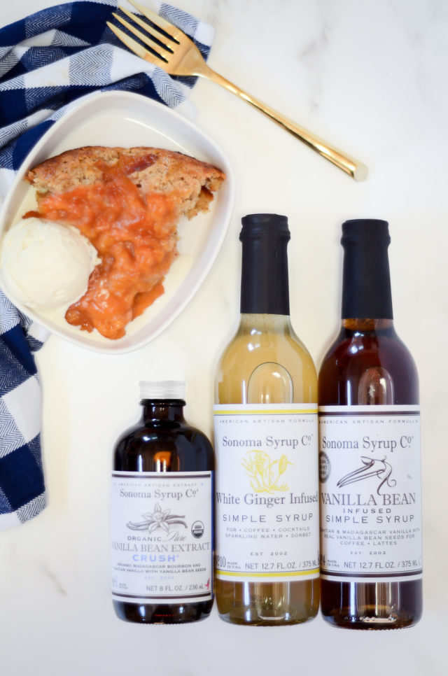 Three bottles of Sonoma Syrup Co. products and a slice of cobbler on a plate.