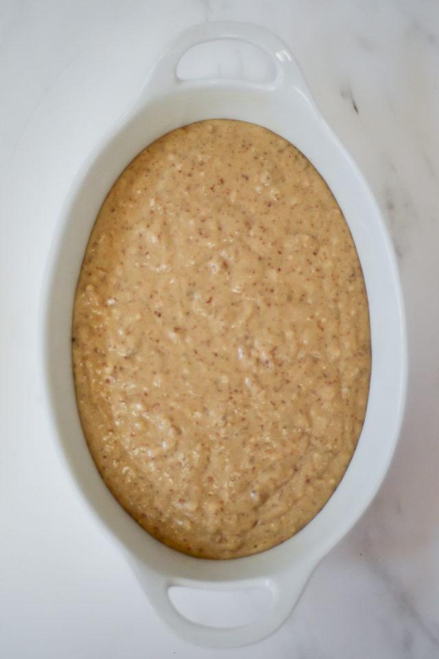 An overhead shot of cobbler batter in a baking dish.